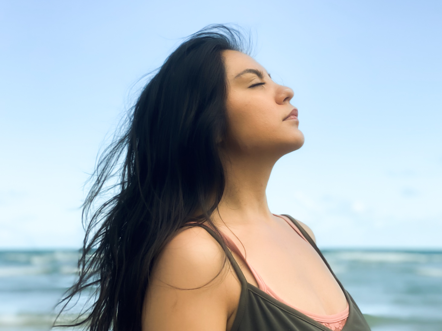 Writer, Victoria Alondra stands with her right shoulder at the forefront of the picture. Her chin is slightly raised and she has long dark wavy hair that sits loose. The blurry background is of the sky and a body of water.