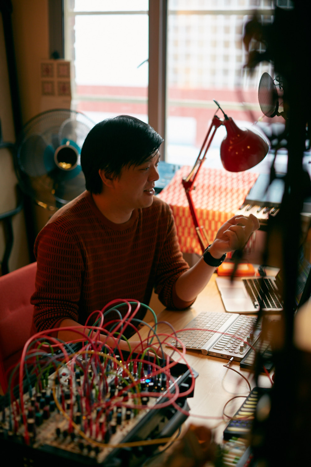Audio producer, Jon Tjhia, sitting at a desk with computers and technical audio equipment. The audio equipment has lots of red and green wires and is sitting in the bottom-left of the shot. Jon is wearing a red long sleeved top and has short dark hair. There is a red lamp next to him and a blue fan in the background.