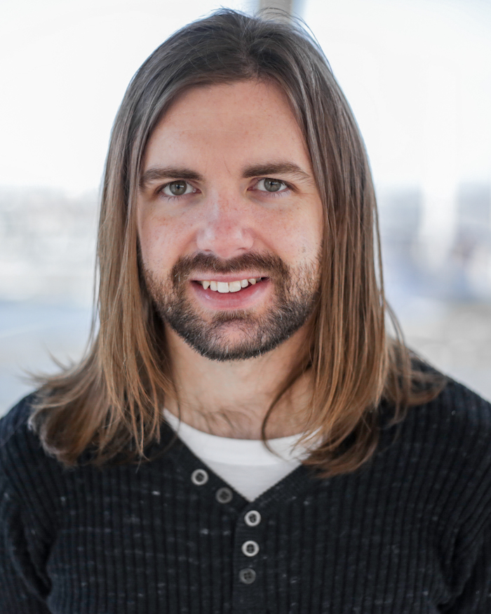 A headshot of the writer Beau Windon. Beau has long brown hair to his shoulders and a neat beard. Beau is wearing a dark coloured sweater over a white tshirt.