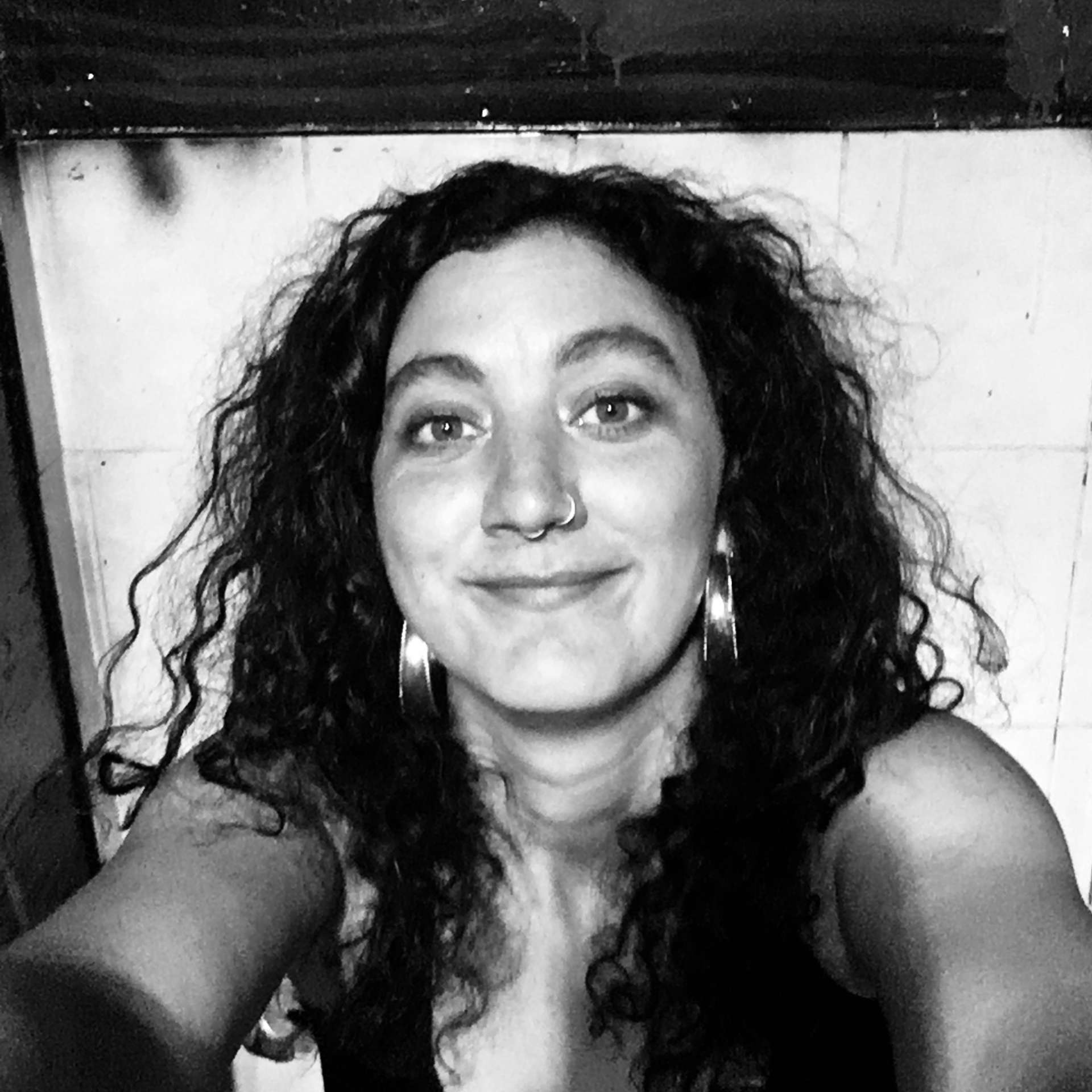 A black and white selfie of the writer, Mykaela Saunders. Mykaela is smiling at the camera and has long curly hair that falls over her shoulders.