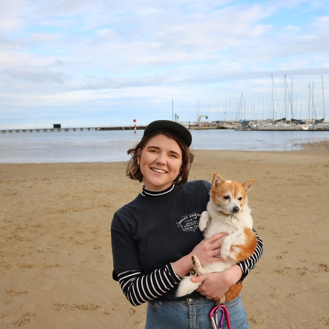 Dani is weatring a black Dolley Parton tshirt and wearing a black cap. They are standing on the beach., holding their dog Foxy and smiling at the camera.